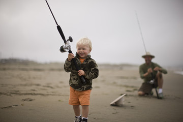 Smiling young toddler carrying a fishing rod while walking along a beach being watched by his father.