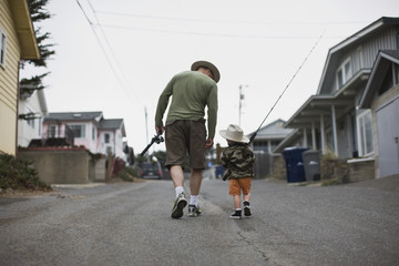 Mid-adult father and his young son walking down a suburban street carrying fishing rods.