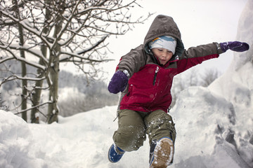 Young boy running through snow.