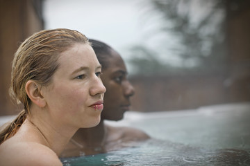 Young woman with a lip ring sitting in a hot tub with wet hair.