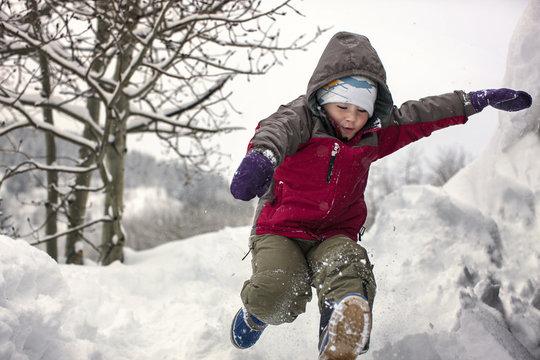 Young boy running through snow.