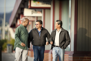 Three smiling middle aged men walking along a street.