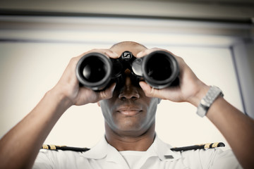 Mid-adult man looking through binoculars while wearing an officer's uniform.