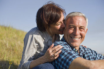 Smiling mid-adult woman nibbling on her husbands ear while sitting together in the country.