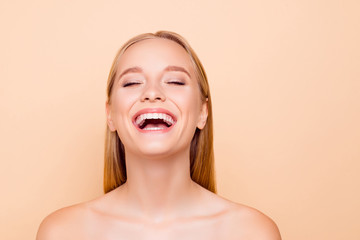 Positive, cheerful, funny, comic, fresh laughing natural nude girl with white teeth fresh cavity smooth soft skin laughing sincerely with close eyes isolated on beige background, perfection concept