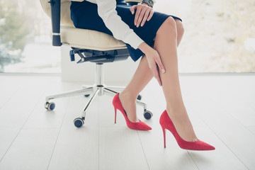 Cropped portrait bottom view of woman's legs wearing black skirt red high heel shoes sitting on armchair touching her perfect smooth soft legs with hand having trouble dry skin, health care concept