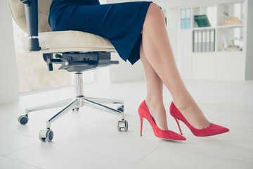 Cropped side view portrait bottom view of woman's legs wearing black skirt red high heels shoes sitting on chair having ideal stunning perfect thin seductive legs, uniform of the company