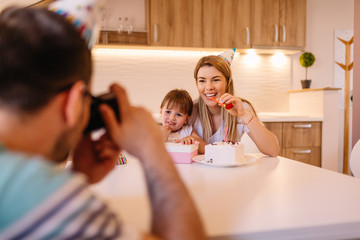 Young father is making photo of his daughter and her mother with birthday cake and gift box