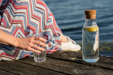 A bottle of water with lemon and a glass. Bridge over the lake and woman.