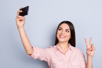 Portrait of pretty, charming, cheerful, positive woman shooting selfie on front camera of gadget, using smart, cell phone, gesturing v-sign with two fingers isolated on grey background