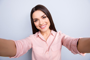 Self portrait of pretty charming cheerful positive cute lovely woman shooting selfie on front camera with two hands isolated on grey background, having video-call with lover