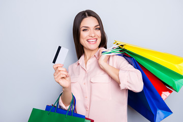Portrait of funny cheerful glad woman in jeans, shirt carrying many colorful bags on shoulder gesturing credit plastic bank card looking at camera isolated on grey background