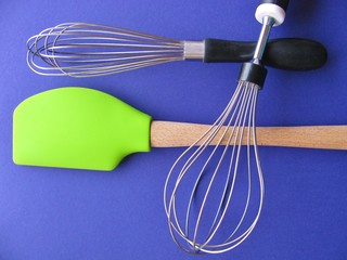 Essential cooking tools: wire whisks and bright, lime green spatula with wooden handle, isolated on purple background.