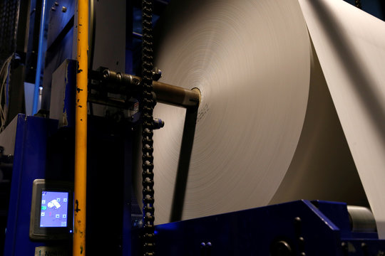 A roll of newsprint paper is fed into a web offset printing machine as the daily newspaper Times of Malta is printed at Progress Press in Mriehel