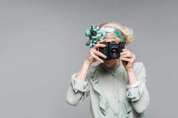 stylish senior woman taking photo with vintage film camera isolated on grey