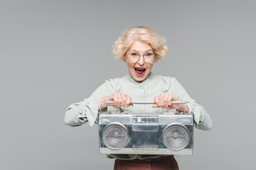 shouting senior woman with boombox isolated on grey