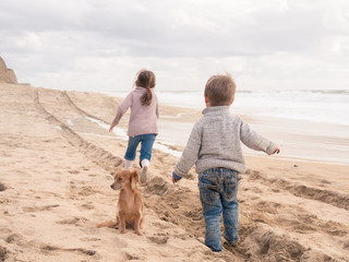 Happy kids with cute dog running on the beach on vacation