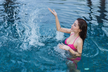 woman in pool and playing water splash