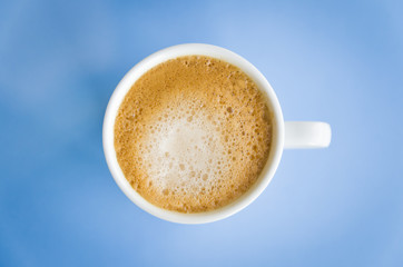 White cup of coffee on light blue background.