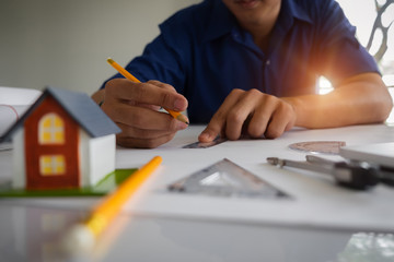 Architect man working with his plan and blueprints for architectural plan, engineer sketching a construction project concept.