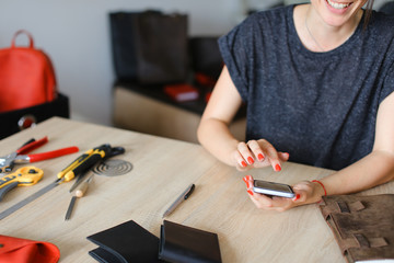 Craftswoman with red nails looking for ideas by smartphone near handmade notebook at leather atelier. Concept of handicraft home business and internet.