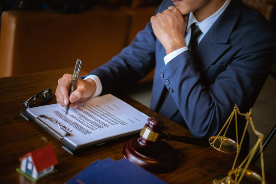 Lawyer businessman writing a contract in office workplace for consultant lawyer concept.