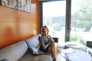 Pretty woman sitting on grey sofa near window at home. Concept of interior designer and apartments.