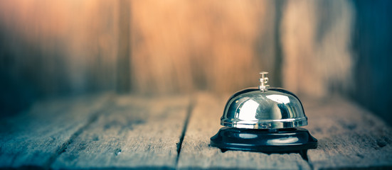 Bell metal service on wood ground with blurred wooden background. Panorama crop size Wall mural