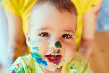 The small baby has paints on the face