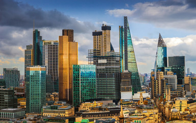 London, England - Panoramic skyline view of Bank and Canary Wharf, central London's leading financial districts with famous skyscrapers at golden hour sunset with blue sky and clouds