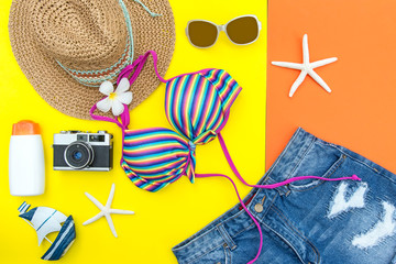 Summer Fashion woman swimsuit Bikini, camera, fish star, sunblock, sun glasses, hat. Travel in the holiday pastel background.  Summer Concept.