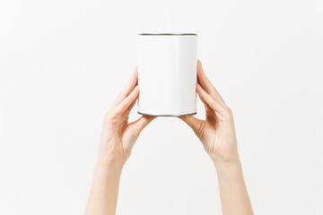 Close up of female hands vertical holds white empty paint tin can with copy space isolated on white background. Instruments, tools for renovation apartment room. Repair home concept. Advertising area.