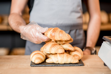 Serving croissants on the plate at the bakery
