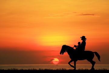 Fototapeta silhouette cowboy and son riding horse on sunrise.