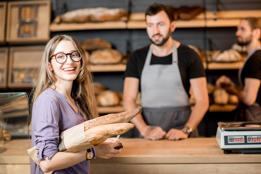 Woman buying bread in the bakery shop with man sellers