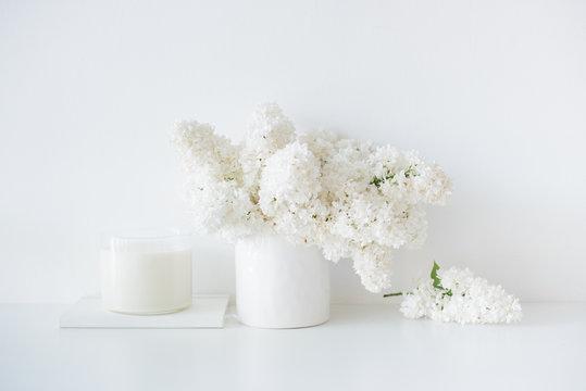 Minimalist white home decor, fresh lilac flowers bouquet in vase