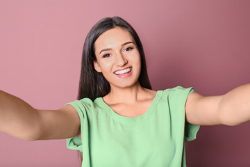 Young beautiful woman taking selfie against color background