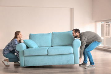 Young couple lifting sofa in empty room. Moving day