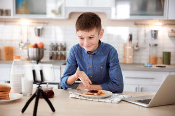 Cute little blogger with food recording video on kitchen