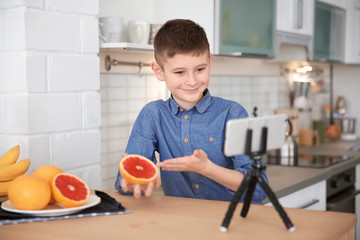 Cute little blogger with grapefruit recording video on kitchen