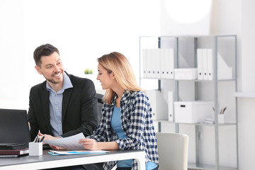 Businessman consulting young woman in office