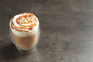 Glass with delicious caramel frappe on grey background