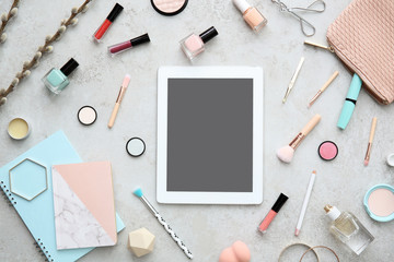 Flat lay composition with tablet and makeup products on grey background