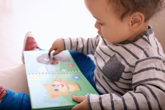 Cute little child with colorful book at home, closeup