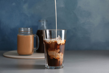 Pouring milk into glass with cold brew coffee on table