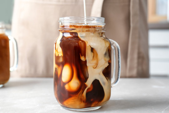 Pouring milk into mason jar with cold brew coffee on table