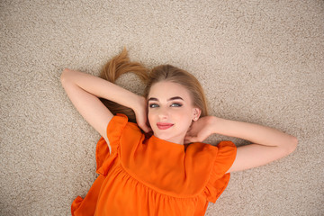Young woman lying on floor at home, top view