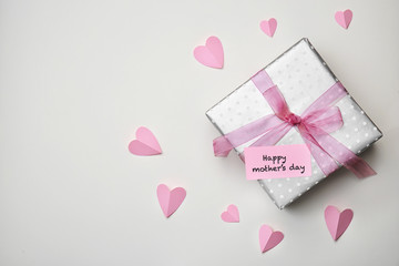 Flat lay composition with paper hearts and elegant gift box for Mother's Day on light background