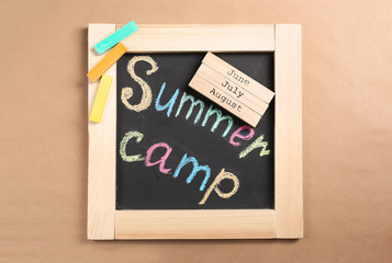 Composition with block calendar and words SUMMER CAMP written on small blackboard, top view