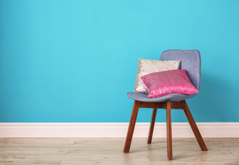 Different pillows on chair near color wall in room